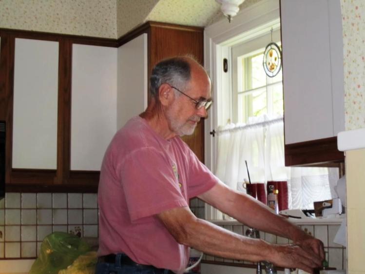 """My dad at the kitchen sink. You can't tell but he's wearing his favorite """"Life is Good"""" Shirt, the one with the dog wearing the backpack."""