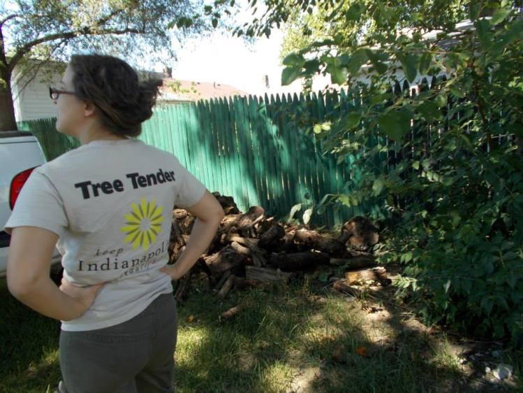 Permaculture designer Katherine supervises unloading of logs for hugelkultur.
