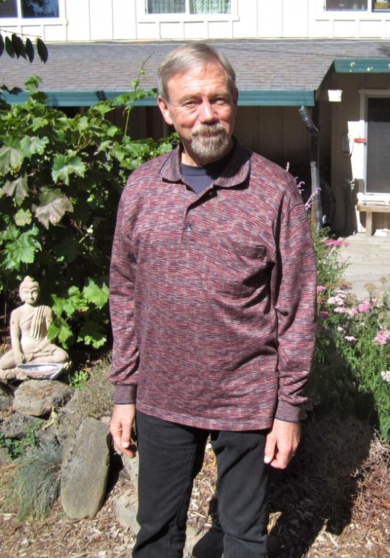 Permaculture instructor Toby Hemenway, with Buddha, in his garden.