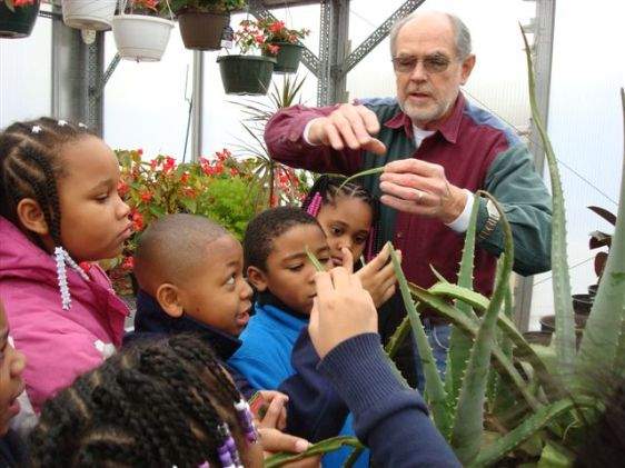 Dad showing grade schoolers the wonders of aloe in the greenhouse.