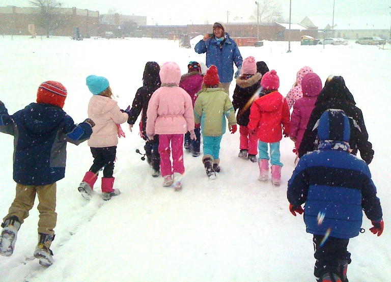 Jen Davies leads a group of small learners on a winter outing to catch snowflakes and look at their shapes.