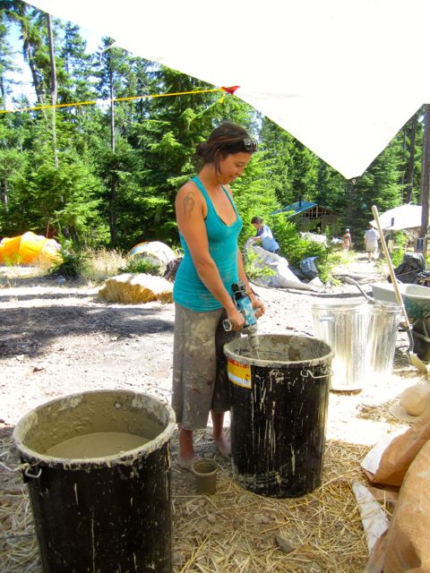 Molly mixing clay slip with a giant eggbeater-type tool.